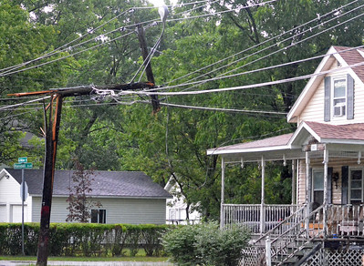KYLE MENNIG - ONEIDA DAILY DISPATCH A splintered telephone pole stands next to a house on the corner of North Willow Street and Randall Avenue following a storm in the City of Oneida on Wednesday, July 13, 2016.