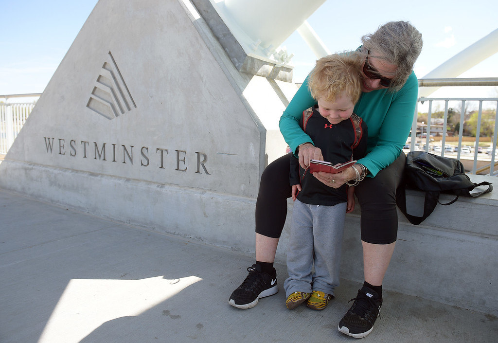 . Jack Coates, 3, and his grandmother Sandy Coates look at Easter photos before they board train at the RTD Light Rail station in Westminster Tuesday.  Lewis Geyer/Staff Photographer April 18, 2017