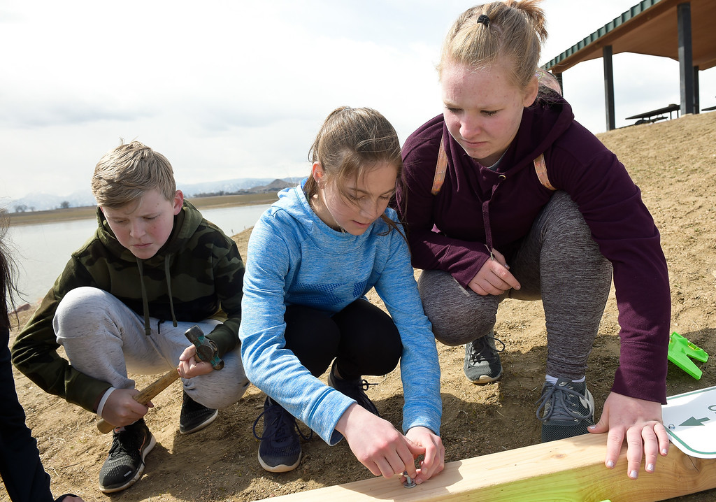 . LONGMONT CO - MARCH 19: From left: Westview Middle School eighth grader Riley Tengwall, seventh grader Fiona Henry, and seventh grader Jade Seamons install bolts on a cedar post for a fishing line collection tube at Lagerman Reservoir March 19, 2019. A total of three collection tubes will be along the north shore. To view more photos visit timescall.com. (Photo by Lewis Geyer/Staff Photographer)