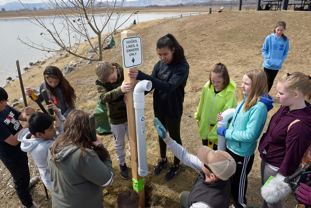 . LONGMONT CO - MARCH 19: Westview Middle School eighth graders Riley Tengwall and Victoria Cordova hold the cedar post with a fishing line collection tubes they were installing at Lagerman Reservoir March 19, 2019. A total of three collection tubes will be along the north shore. To view more photos visit timescall.com. (Photo by Lewis Geyer/Staff Photographer)