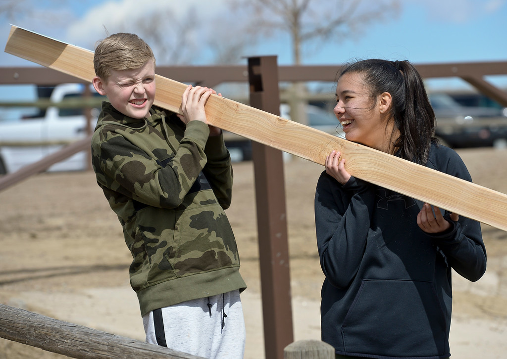 . LONGMONT CO - MARCH 19: Westview Middle School eighth graders Riley Tengwall and Victoria Cordova hold a cedar post while a hole was being dug for it at Lagerman Reservoir March 19, 2019. A total of three fishing line collection tubes will be along the north shore. To view more photos visit timescall.com. (Photo by Lewis Geyer/Staff Photographer)