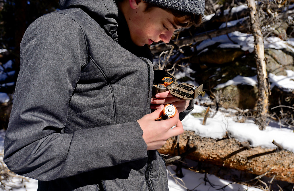 . Skyline High School student Dylan Tusinski, 15, who attended Westview Middle School, puts new batteries into a game camera with students from Westview Middle School at Rocky Mountain National Park on Wednesday. More photos: TimesCall.com. Matthew Jonas/Staff Photographer March 1,  2017