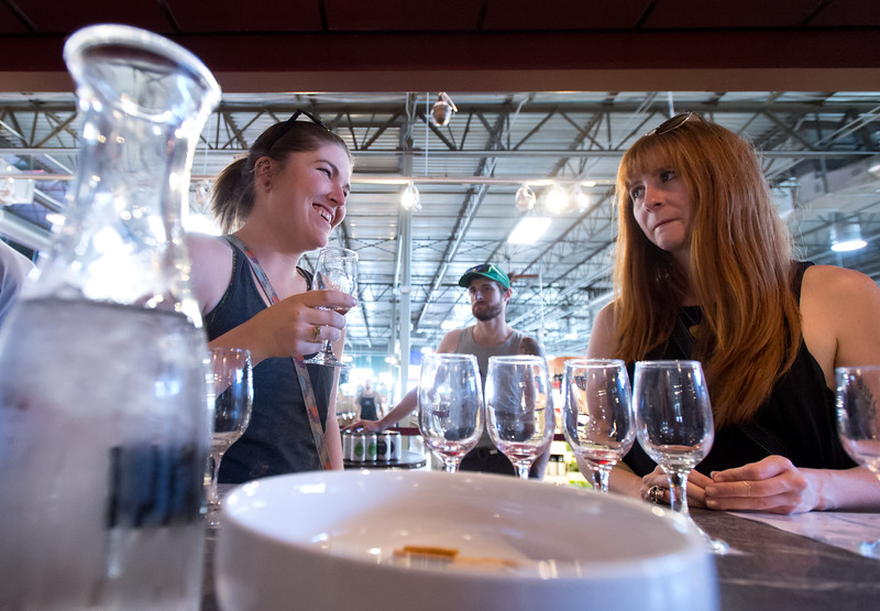 "Jesse Henderkott (left) and Kate Derksen drink wine during a tasting at Wyatt's Wet Goods in Longmont on Saturday. One of the managing partners of Wyatt's asked city council earlier this month to remove restrictions on the number of tastings a store can have, to line it up with the state law. The council will vote on the ordinance on Tuesday.<br /> More photos:  <a href=""http://www.dailycamera.com"">http://www.dailycamera.com</a><br /> (Autumn Parry/Staff Photographer)<br /> July 23, 2016"