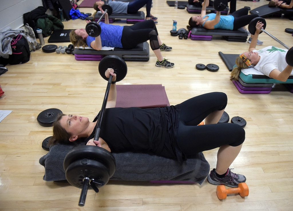 . Tori Guess lays on her back with a barbell during the BODYPUMP workout at the Arapahoe YMCA, 2800 Dagny Way, Lafayette, Wednesday morning. To view more photos visit dailycamera.com. Lewis Geyer/Staff Photographer Dec. 06, 2017
