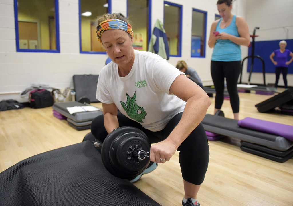 . Karrie Bach adds weight to her barbell during the BODYPUMP workout at the Arapahoe YMCA, 2800 Dagny Way, Lafayette, Wednesday morning. To view more photos visit dailycamera.com. Lewis Geyer/Staff Photographer Dec. 06, 2017