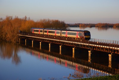 170638 on the L42 1322 Birmingham New Street to Cambridge crosses the Hundred foot drain, Ouse Washes on the 19th January 2020