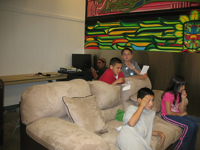 "David and the kids in the ""technology"" room. David did the mural that's on the wall behind him. That's Elvis in the grey shirt and Vanessa in the pink. They are watching TV and getting the Wii set up."