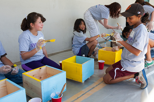 Children in the kid's area painting cubbies for the school.