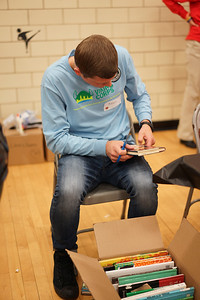 Adam, a volunteer and Viking Corps member, removes library markings and labels from books donated by the Cleveland Kids' Book Bank. Books will be given to students in CMSD schools