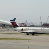 Delta Airlines Boeing 717 N978AT taxies at Newark Airport while JetBlue Airbus A320 N807JB takes off behind.