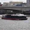A City Cruises catamaran passing under London Bridge on the Thames.