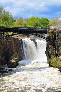 Day 125: Great Falls Paterson NJ- May 5.   After the large amount of rainfall that we had last week, the Great Falls were an awesome sight as water from the swollen Passaic River flowed over the falls.  During the late fall and winter months, the water flow was very low.  For a sense of perspective, the bridge over the top is a pedestrain walkway so folks can vew the falls from above and the railing height at the top of the bridge is just under 5 feet. The people in the photo look like miniature dolls.