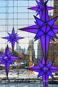 "Day 352: TimeWarner Center - December 19. Part of the Time Warner Center ""Holiday Under the Stars"" display. Taken from inside the building with a view of Columbs Circle and Central Park South. The display consists of 12 14ft stars that hang from the ceiling in the lobby area of the center. The stars continually change color - managed by the largest display of illuminated color-mixing in the world. I'd love to get back one evening to see the lights against a darker night background"