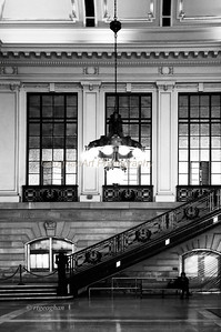 Day 71: Erie-Lackawanna Terminal Waiting Room Hoboken NJ - Mar 12.   After severe flood damage from Superstorm Sandy, this old and loved train and ferry terminal in Hoboken reopened about 3 weeks ago.  Fortunately the beautiful old lighting fixtures and iron railing in the Greek Revival style Waiting Room appear to be undamaged, But all of the lovely old wooden benches and shoeshine stand are boarded and covered up.  Don't know how badly they were damaged or if they can be restored. Even though the Wiaiting Room is open, all of the lower level ticket windows are boarded up and have not reopened.  A close look at this image wll show that all of the lower level windows are covered with plastic and sealed. The terminal serves more than 50,000 commuters daily who use trains, PATH, NJ Light Rail, bus and ferry services.