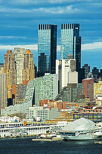 A vertical format scene of  layers of buildings of the New York Skyline as the sundown hour begins.  The Intrepid Air and Space Museum can be seen at the Hudson River waterfront while above and behind, the two towers of the Time Warner Complex appear to stand guard.  The Time Warner Center is a mixed-use building complex, located at  Columbus Circle, across from the southwest corner of Central Park.  The twin office and residential towers  are joined by a multi-story atrium at street level with retail shops and eateries.  The complex also houses the Mandarin Oriental New York hotel.  Constructed as the AOL Time Warner Center, the offices of WarnerMedia (formerly Time Warner) and an R&D center for VMware are located there but will soon move to the new Hudson Yards area further south in midtown.  The Time Warner building will be renamed when the move is completed and a new anchor tenant takes over the space.