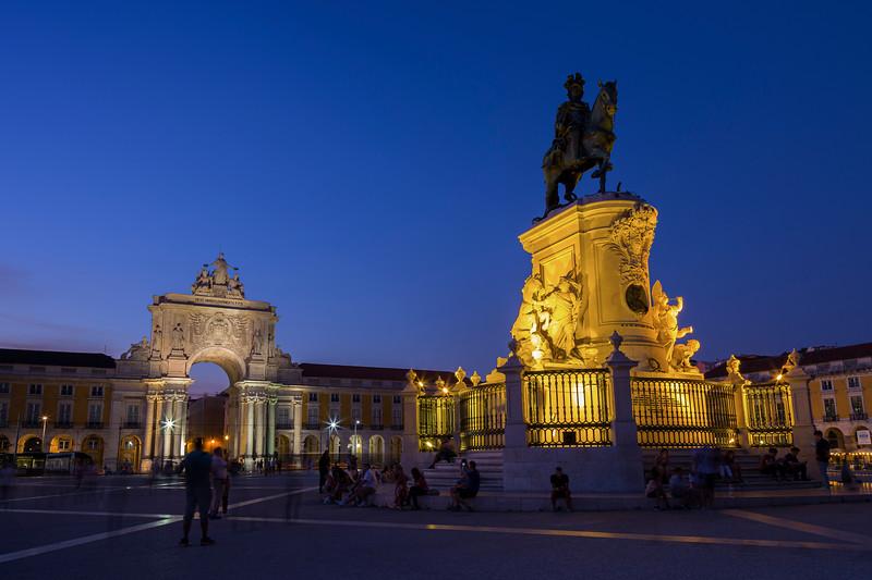 Arco da Rua Augusta, people and statue at Praca do Comercio in Lisbon at dusk