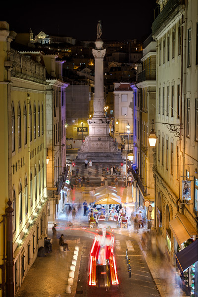 Statue at the Rossio Square and street in Lisbon at dusk