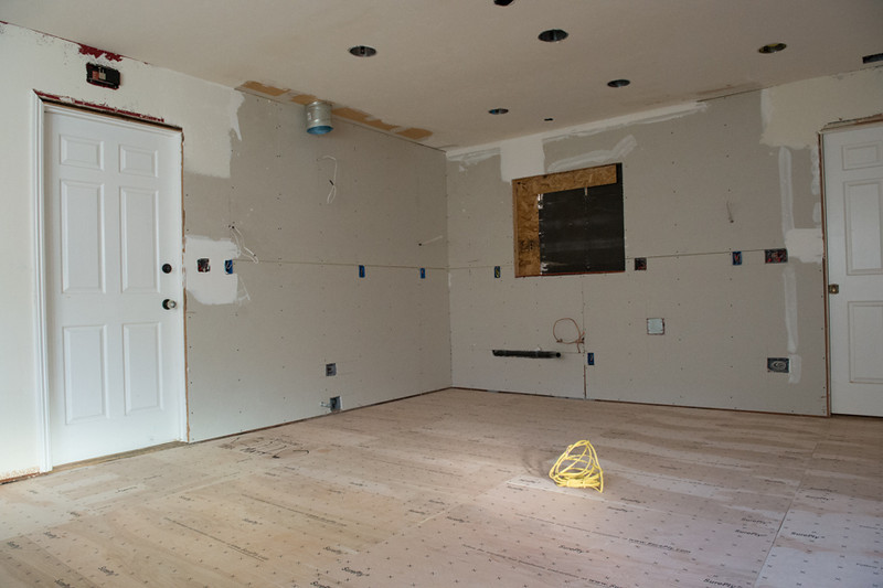 """Rough plumbing & electrical in.  New sheetrock and texturing.  Waiting on window.  After lifting the laminate, there was linoleum and 3/4"""" plywood.  Both had to be removed and this 1/4"""" plywood applied before flooring could go in."""