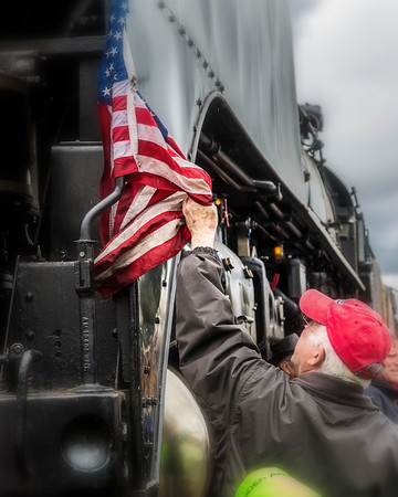 A veteran reaches to untangle Old Glory on UP844.