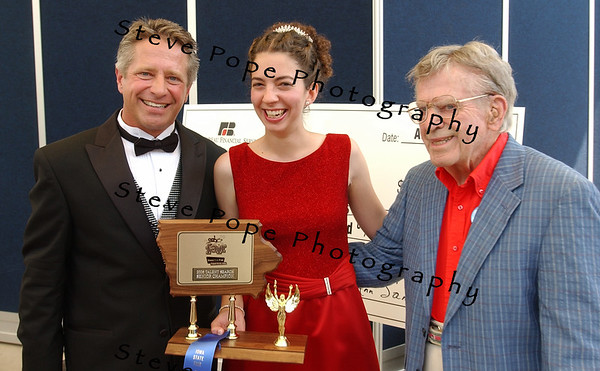 Amanda Hardy, 21, of Prole, IA, receives her plaque and $7500 award from Bill Riley Jr. (left) and Bill Riley Sr. (right) after placing first with her oboe solo in the Bill Riley Talent Search on the Bill Riley Stage ta the 2006 Iowa State Fair in Des Moines, IA, on Sunday, August 20, 2006.  (Iowa State Fair Photo)