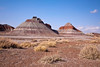 """Tepees"".  The white layers are sandstone.  The cap of the tepees is clay.  The red layers are iron-stained siltstone."