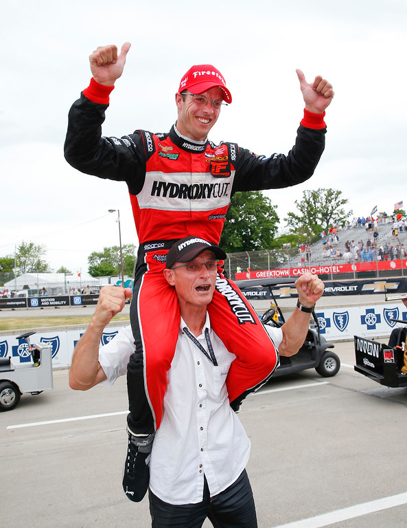 . Sebastien Bourdais, of France, celebrates on the shoulders of his father, Patrick, after winning race one of the IndyCar Detroit Grand Prix auto racing double header on Belle Isle in Detroit, Saturday, June 4, 2016. (AP Photo/Paul Sancya)