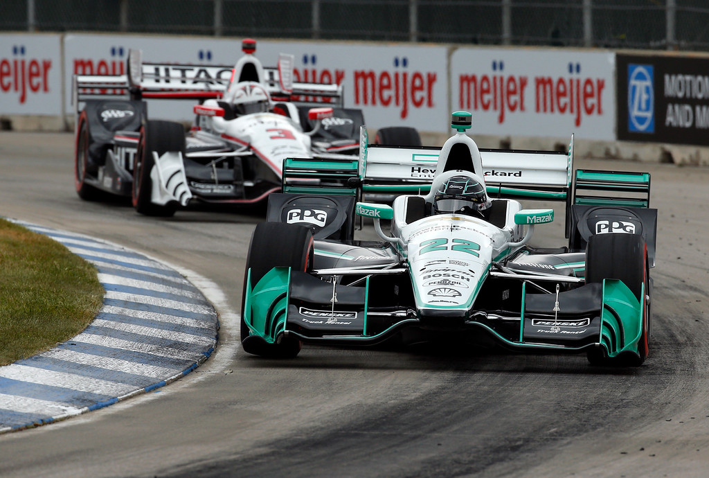 . Simon Pagenaud (22) leads Helio Castroneves into a turn during race one of the IndyCar Detroit Grand Prix auto racing doubleheader on Belle Isle in Detroit, Saturday, June 4, 2016. (AP Photo/Paul Sancya)