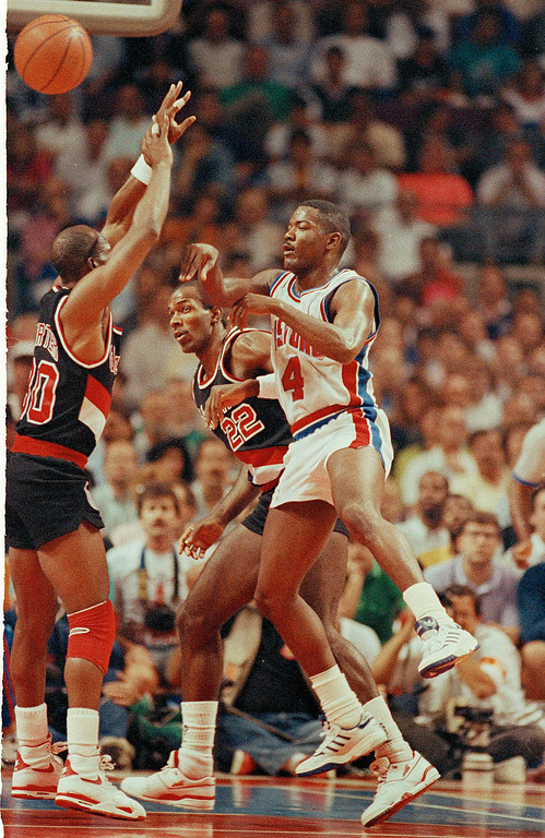 . Detroit\'s Joe Dumars passes off over Portland\'s Terry Porter, left, during the first quarter of Game 2 in the NBA Finals at the Palace in Auburn Hills, Mich., June 7, 1990.  In back for the Blazers is Clyde Drexler.  (AP Photo/Lennox McLendon)