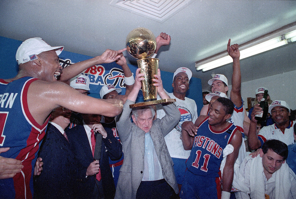 . Detroit Pistons team owner Bill Davidson holds the Larry O\'Brien Trophy surrounded by his players following their NBA championship victory over the Los Angeles Lakers in game 4 in Inglewood, Ca., June 13, 1989.   From left are, Rick Mahorn, Davidson, John Salley, and Isiah Thomas (11).  Detroit completed the fifth sweep in NBA Finals history with their 105-97 victory.  (AP Photo/Doug Pizac)