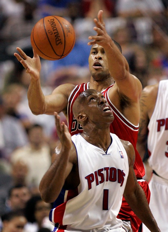 . Chicago Bulls forward P.J. Brown reaches over Detroit Pistons guard Chauncey Billups (1) for the ball during the first quarter of an Eastern Conference semifinal NBA playoff basketball game at the Palace of Auburn Hills, Mich., Tuesday, May 15, 2007. (AP Photo/Carlos Osorio)