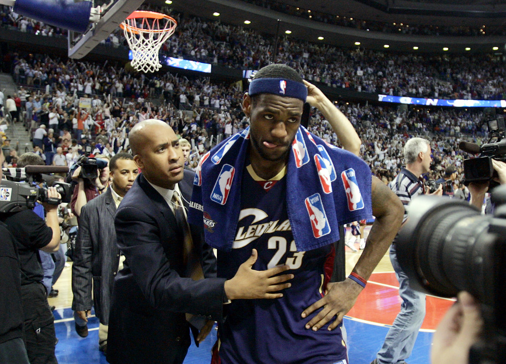 . Cleveland Cavaliers forward LeBron James walks off the court after the Detroit Pistons defeated the Cavaliers 79-61 in Game 7 of the NBA basketball playoffs at the Palace in Auburn Hills, Mich., Sunday, May 21, 2006. Man at left is unidentified. (AP Photo/Paul Sancya)