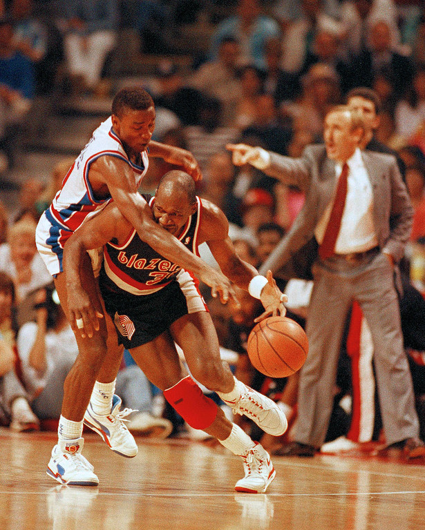 . Detroit\'s Isiah Thomas, left, reaches over Portland\'s Terry Porter during the third quarter of Game 2 in the NBA finals in Auburn Hills, Mich., June 7, 1990.  (AP Photo/Lennox McLendon)