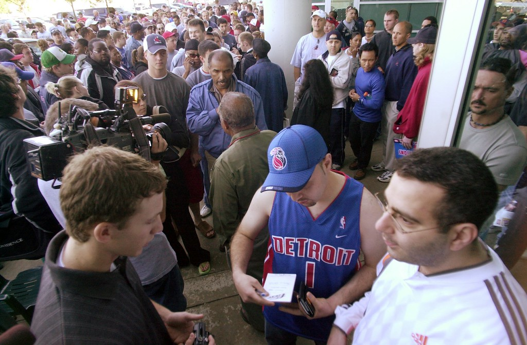 . Hundreds of Detroit Pistons fans line up outside the Palace in Auburn Hills, Mich., Thursday, June 3, 2004, for a chance to buy NBA Finals playoffs tickets against the Los Angeles Lakers. In the foreground are the first ticket buyers Jevano Kakos in white and Hammod Sobh in the Pistons jersey. (AP Photo/Carlos Osorio)
