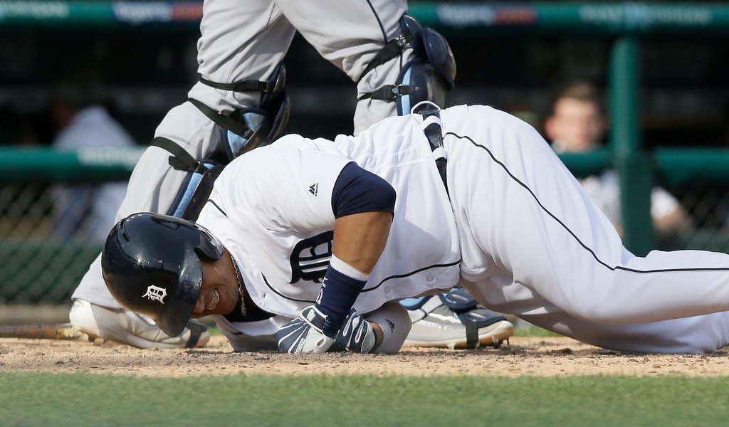 . Detroit Tigers designated hitter Victor Martinez falls to the ground after swinging at a change up pitch during the seventh inning of a baseball game against the Tampa Bay Rays, Saturday, May 21, 2016, in Detroit. (AP Photo/Carlos Osorio)