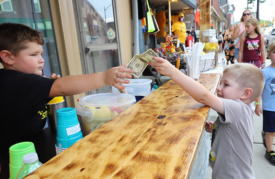 Maddox Rice, 5, of Fombell serves up a lemonade to Hunter Faust,4, of Zelienople at Rice's lemonade stand during Thursday's Open Air Market on Main Street. Seb Foltz/Butler Eagle 08/13/20