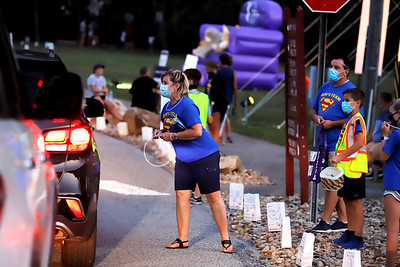 Joan McConahy of Zelienople collects donations at Saturday's American Cancer Society luminary drive fundraiser in Cranberry Community Park Saturday with her son Mark, 13, and husband Dave. Representing Sam's Team, the McConahys lost their other son Sam to brain cancer at age 7, and Sam and Mark's grandfather John Graph to leukemia at age 80. Seb Foltz/Butler Eagle