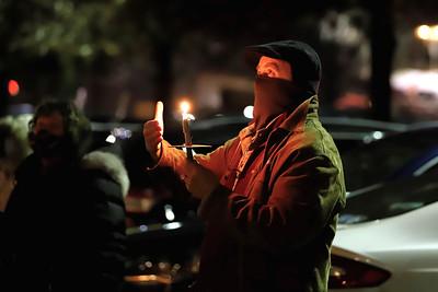 Pastor John Silbert of the Covenant Presbyterian Church in Butler tends to his candle at Tuesday night's prayer vigil outside of Butler Memorial Hospital. Seb Foltz/Butler Eagle 12/22/20