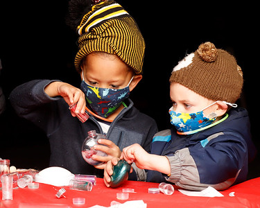Evan Stalnaker, 4, (left) and Zaire Bunnel, 4, work on their ornaments at the Ginger Hill Tavern's ornament and letters to Santa station during Slippery Rock's Christmas Market Saturday night. Seb Foltz/Butler Eagle 11/21/20