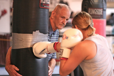 Butler Cubs boxing manager Don Spinetti holds the heavy bag during a training session with Marli Knox, 16, of Karns City. Seb Foltz/Butler Eagle 09/23/20