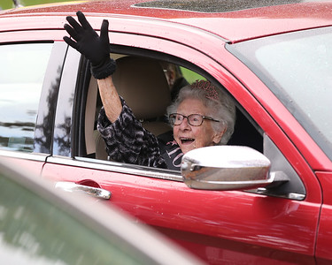 Madeleine Samarco of Cranberry waves to passers by during her 100th birthday drive-by parade Saturday. Samarco sat in a vehicle while a line of cars passed waving and delivering gifts to her daughters. Seb Foltz/Butler Eagle. 10/24/20