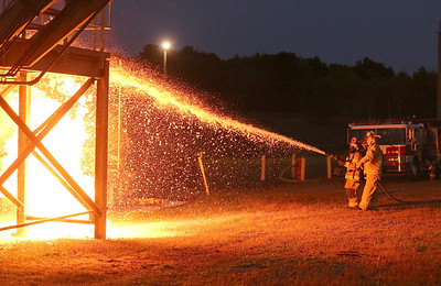 Fire certification specialist Jason Bragunier(right) directs students fighting a simulated truck fire during fire training at Butler County Community College Wednesday. Seb Foltz/Butler Eagle 09/16/20