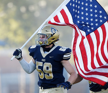 Eli Reese, a senior at Knoch High School, carries the American flag onto the field Friday, September 11, 2020, for the game with Highlands. Harold Aughton/Butler Eagle:
