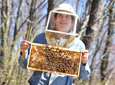 After a long winter, Luke Chambers of Jackson Twp. examines the health of one of his hives. Harold Aughton/Butler Eagle. March 30, 2021.