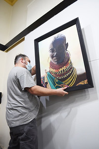 """Brad Page, 48, a Butler Arts Center board member, in the process of hanging an oil painting by Marilyn Tynan titled """"Tarkana Tribal Woman""""  while preparing the gallery on April 6, 2021 for the art center's first show  since the pandemic on April 16 called """"Art is..."""" Tynan was one of 30 artists whose art was selected for the show.  Photo by Lauryn Halahurich/Butler Eagle"""