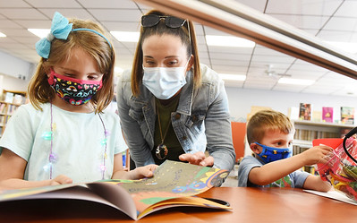 """Harper Tempalski, 6, checks out the """"Bugging Out Bag"""" she received at the South Butler Library with her mother, Nicole Tempalski and her 4-year-old brother, Lachlan, Wednesday, April 14, 2021. Harold Aughton/Butler Eagle."""