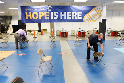 Butler Health System environmental services employees Don Woodward, left, and Kirk Eury, setup tables and chairs at the former Sears building at the Clearview Mall Tuesday afternoon. April 13, 2021. Harold Aughton/Butler Eagle.