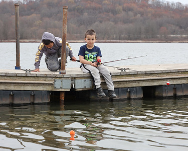 A.J. Lyles sits and waits for a fish to bite at Moraine State Park Saturday while his brother Julian, 7, looks for fish through a crack in the dock. According to the Pennsylvania Fish and Boat Commission, the first Saturday before trout season is  Mentored Youth Trout Fishing Day, a day where children can fish without a license under the supervision of a licensed adult. Seb Foltz/Butler Eagle 03/27/20