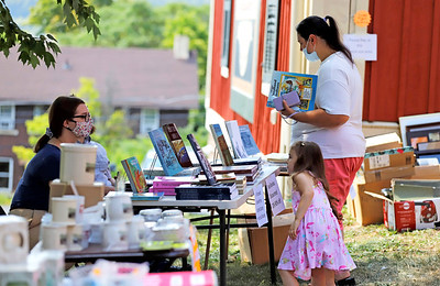 Sunday Volpe and her daughter Nina, 4, of Center Township look at books at Lowrie House yard sale Saturday. Seb Foltz/butler Eagle 08/22/20