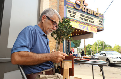 Carmen Bianco of Connequenessing stitches a together a leather wallet at his table outside of Curio Cool in Zelienople during the town's weekly Open Air Market Thursday. Seb Foltz/Butler Eagle 08/13/20