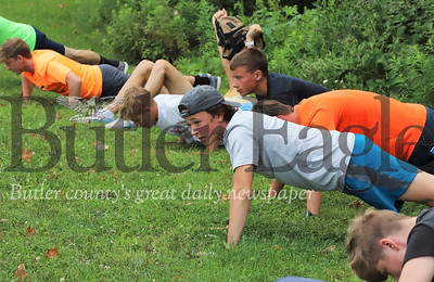 Members of the Butler Area High School Boys Cross County team do push-ups before a practice run Thursday evening. Seb Foltz/Butler Eagle 08/06/20